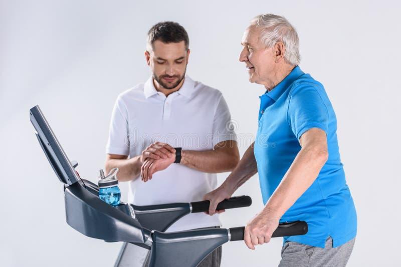θεράπων αποκατάστασης που ελέγχει το χρόνο βοηθώντας το ανώτερο άτομο που ασκεί treadmill στοκ εικόνες