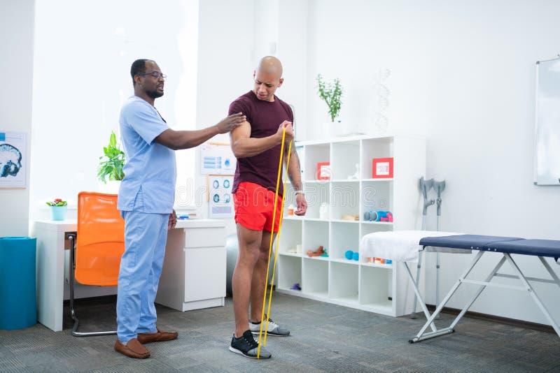 Θεράπων που βοηθά τον αθλητικό τύπο που κάνει τις ασκήσεις για τα όπλα μετά από τον τραυματισμό στοκ φωτογραφία