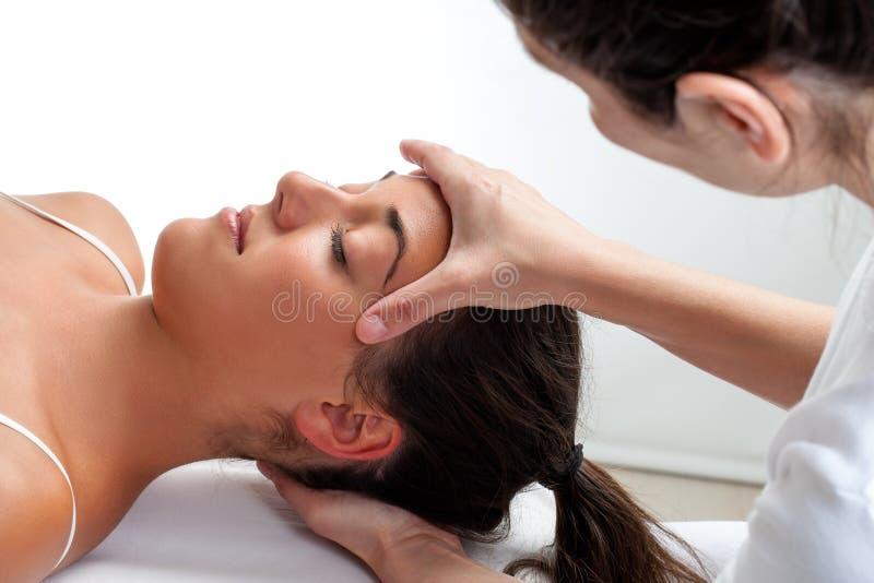 Θεράπων που κάνει τη θεραπεύοντας επεξεργασία στο κεφάλι της γυναίκας στοκ φωτογραφία