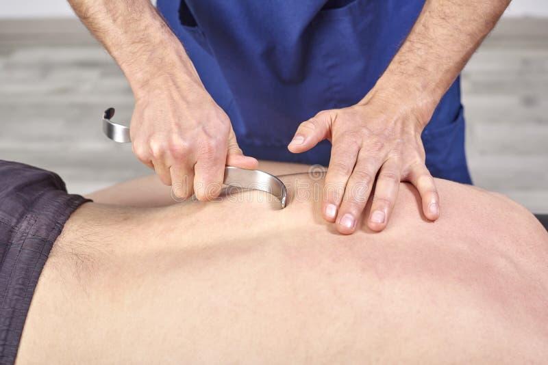 Θεράπων που κάνει diacutaneous Fibrolysis, των γάντζων που θεραπεύουν την επεξεργασία σε man& x27 πλάτη του s r Chiropractic, στοκ φωτογραφίες