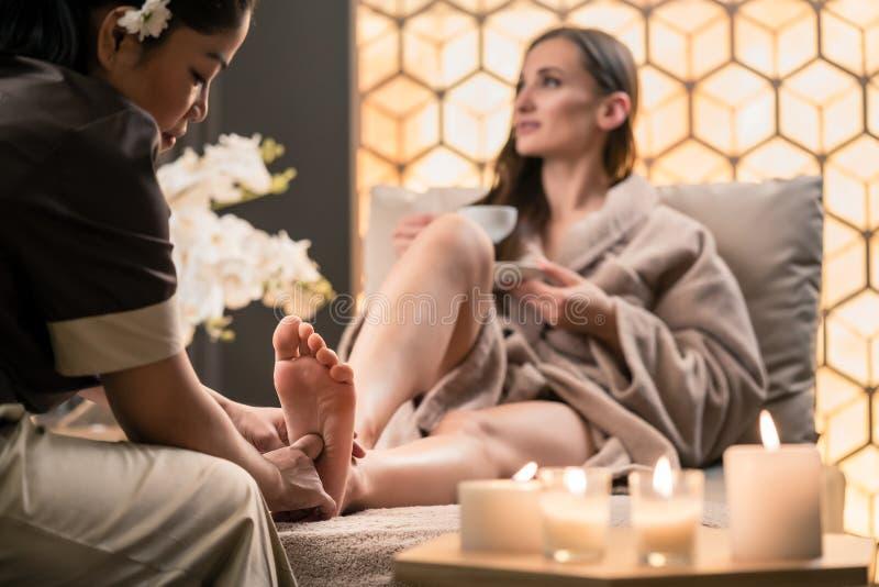 Θεράπων που τρίβει το πόδι ενός θηλυκού πελάτη στην ασιατική ομορφιά στοκ εικόνες