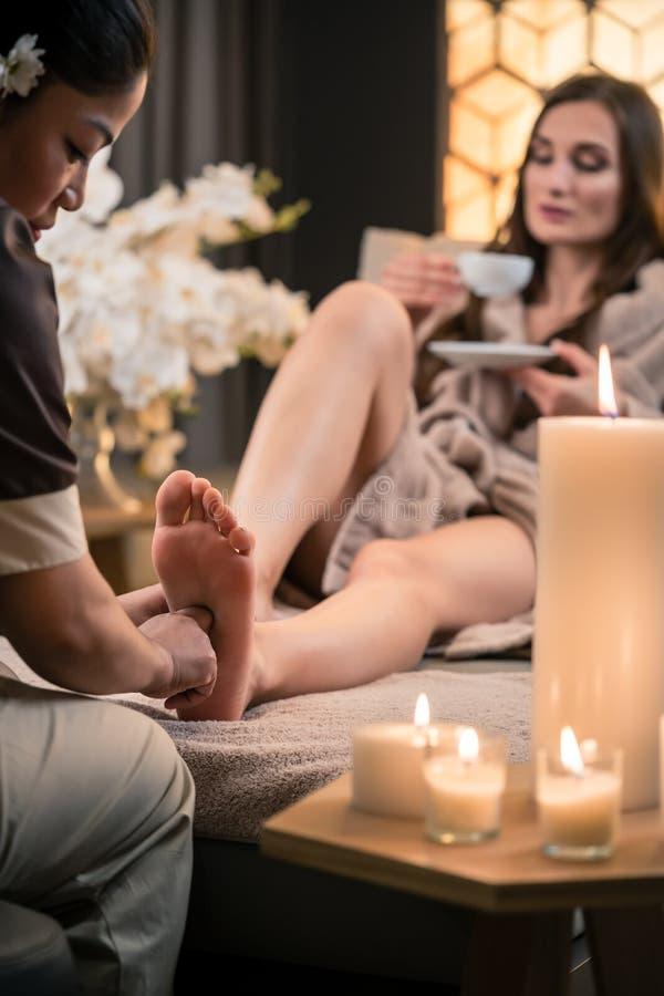 Θεράπων που τρίβει το πόδι ενός θηλυκού πελάτη στην ασιατική ομορφιά στοκ εικόνα με δικαίωμα ελεύθερης χρήσης