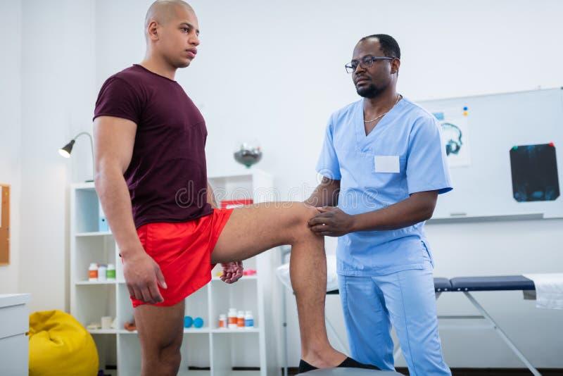 Θεράπων στα γυαλιά που εξετάζει το γόνατο του αθλητικού τύπου μετά από τον τραυματισμό στοκ εικόνες