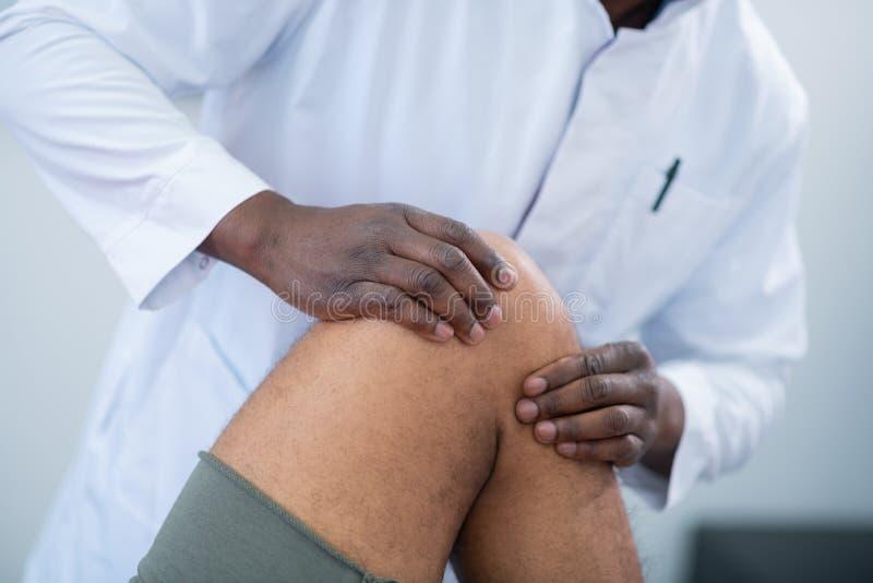 Θεράπων σχετικά με το γόνατο του αθλητικού τύπου που φορά τα γκρίζα σορτς στοκ φωτογραφία