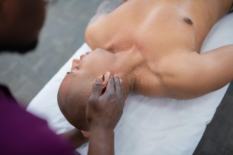 Θεράπων σχετικά με το κεφάλι του αθλητικού τύπου που κάνει το μασάζ λαιμών στοκ φωτογραφία με δικαίωμα ελεύθερης χρήσης