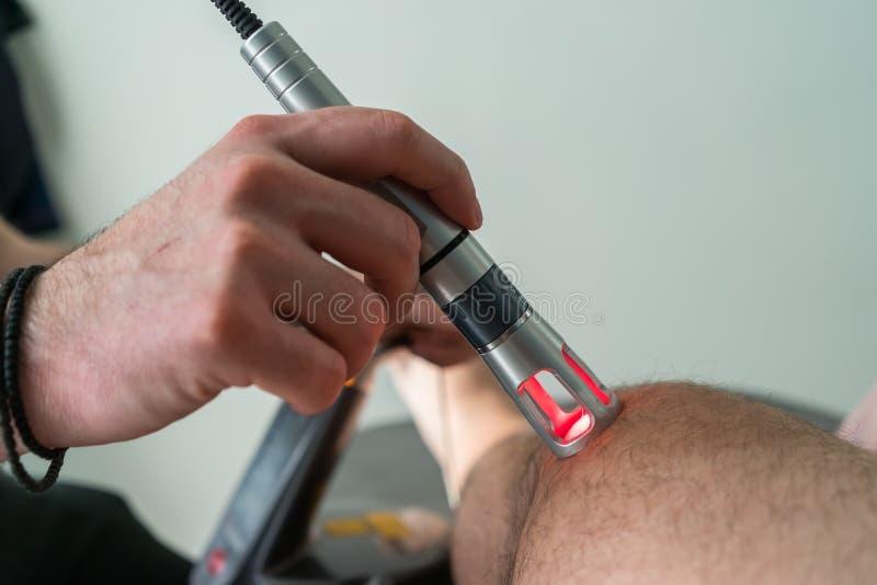 Θεραπεία λέιζερ σε ένα γόνατο που χρησιμοποιείται για να μεταχειριστεί τον πόνο στοκ φωτογραφίες με δικαίωμα ελεύθερης χρήσης