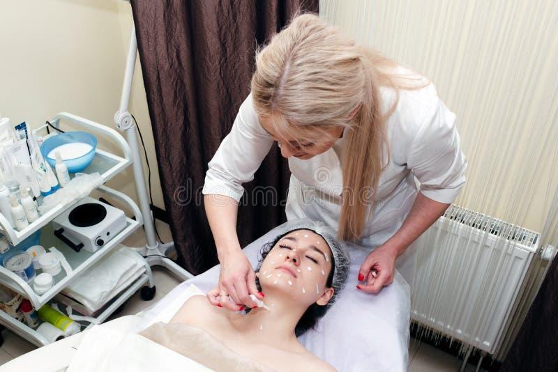 Θεραπεία ή θεραπεία κρέμας προσώπου για το κουρασμένο δέρμα προσώπου Beautician που εφαρμόζει το λοσιόν στο θηλυκό πρόσωπο στο σα στοκ εικόνες