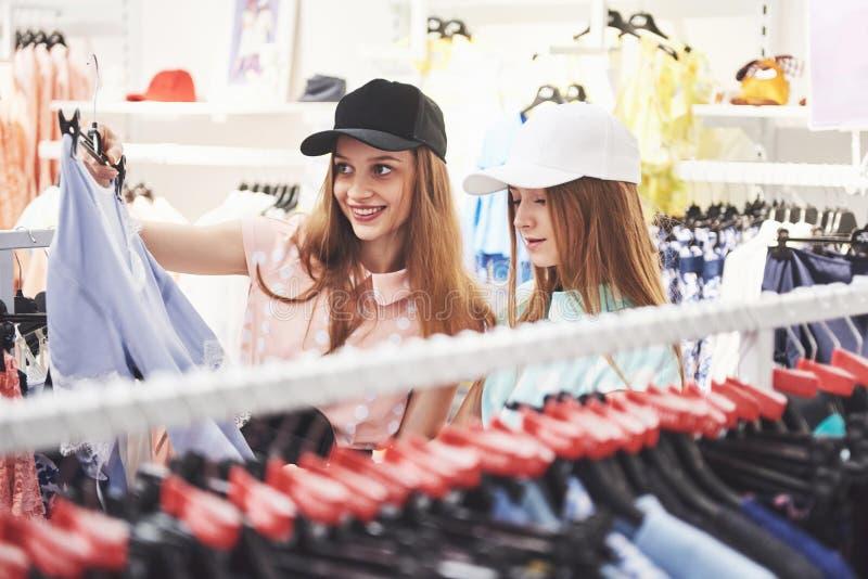 Θεραπεία αγορών στη δράση Οπισθοσκόπος δύο όμορφων γυναικών με τις αγορές τοποθετεί την εξέταση η μια την άλλη με το χαμόγελο σε  στοκ φωτογραφία με δικαίωμα ελεύθερης χρήσης
