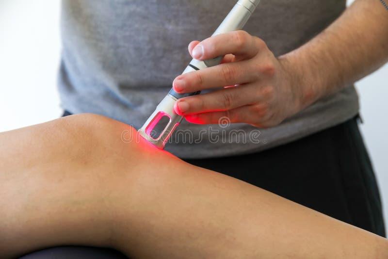 Θεραπεία λέιζερ σε ένα γόνατο που χρησιμοποιείται για να μεταχειριστεί τον πόνο στοκ φωτογραφίες