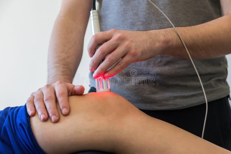 Θεραπεία λέιζερ σε ένα γόνατο που χρησιμοποιείται για να μεταχειριστεί τον πόνο στοκ φωτογραφία με δικαίωμα ελεύθερης χρήσης