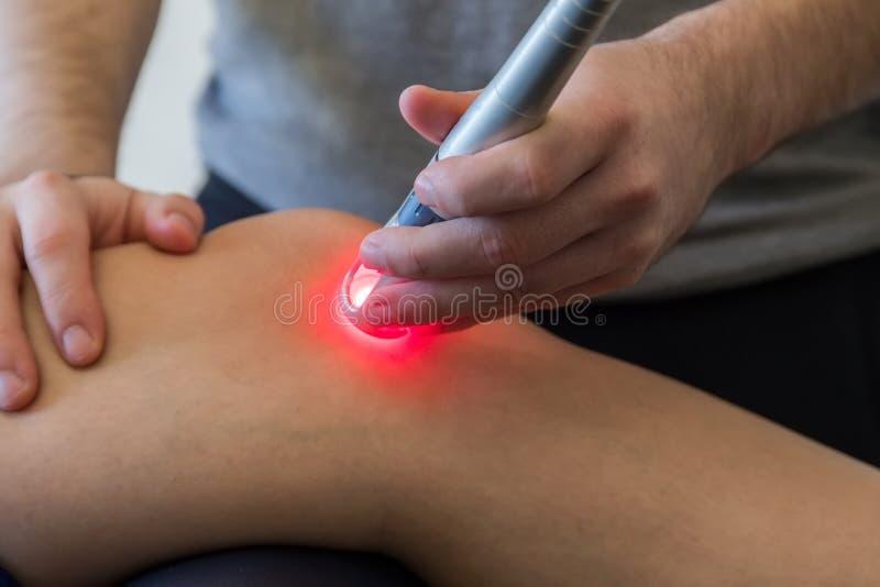 Θεραπεία λέιζερ σε ένα γόνατο που χρησιμοποιείται για να μεταχειριστεί τον πόνο στοκ φωτογραφία