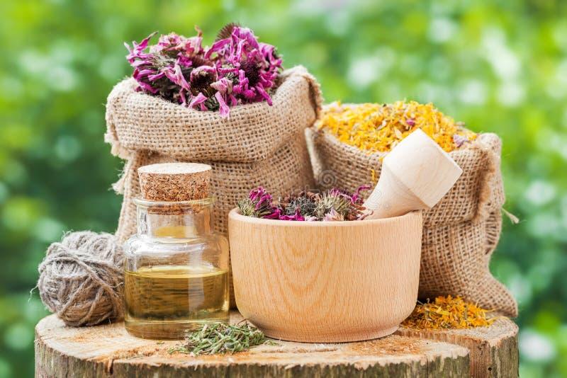 Θεραπεία των χορταριών hessian στις τσάντες, ξύλινο κονίαμα με τα coneflowers στοκ φωτογραφία