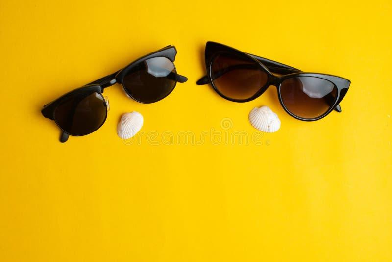 Θερινά εξαρτήματα, κοχύλια θάλασσας και γυαλιά ήλιων ζευγών στο κίτρινο υπόβαθρο Καλοκαίρι, φεγγάρι μελιού και έννοια θάλασσας Co στοκ εικόνα