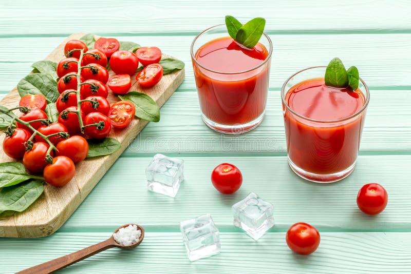 Θερινά κοκτέιλ για τη φρεσκάδα με την κόκκινους ντομάτα και τον πάγο στο πράσινο ξύλινο υπόβαθρο μεντών στοκ εικόνα με δικαίωμα ελεύθερης χρήσης