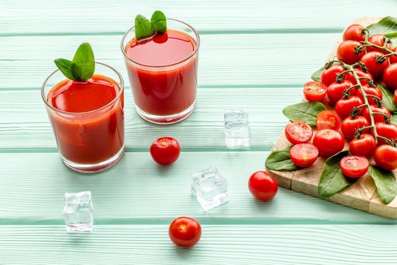 Θερινά κοκτέιλ για τη φρεσκάδα με την κόκκινους ντομάτα και τον πάγο στο πράσινο ξύλινο υπόβαθρο μεντών στοκ φωτογραφία με δικαίωμα ελεύθερης χρήσης