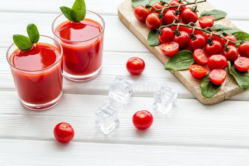 Θερινά κοκτέιλ για τη φρεσκάδα με την κόκκινους ντομάτα, το σπανάκι και τον πάγο στο άσπρο ξύλινο υπόβαθρο στοκ φωτογραφία