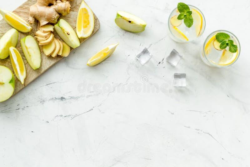 Θερινά κοκτέιλ για τη φρεσκάδα με το μήλο, το πορτοκάλι και τον πάγο στο άσπρο πρότυπο άποψης υποβάθρου τοπ στοκ φωτογραφία
