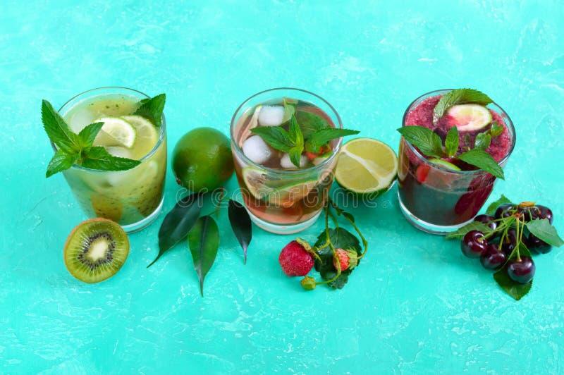 Θερινά κρύα ποτά με τους νωπούς καρπούς, τα μούρα και τη μέντα στοκ εικόνες