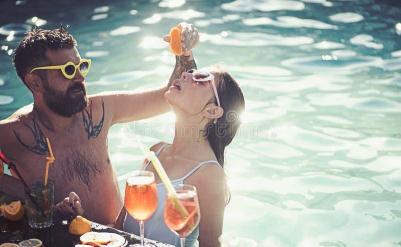 Θερινές διακοπές και κολύμβηση εν πλω Ζεύγος του γενειοφόρων άνδρα και της γυναίκας με το κοκτέιλ και φρούτα στο Μαϊάμι Κοκτέιλ σ στοκ φωτογραφία