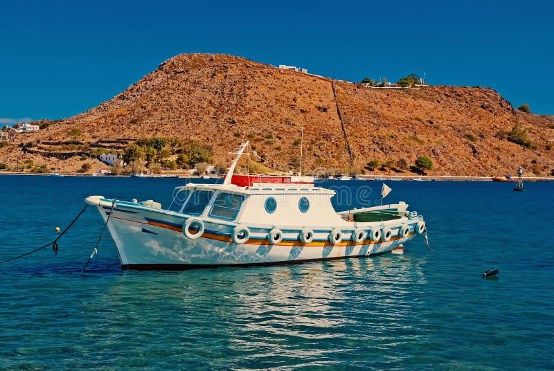 Θερινές διακοπές και ταξίδι θάλασσας Βάρκα στην μπλε θάλασσα σε Patmos, Ελλάδα Μικρό σκάφος στην παραλία με το βουνό στον ηλιόλου στοκ εικόνα με δικαίωμα ελεύθερης χρήσης