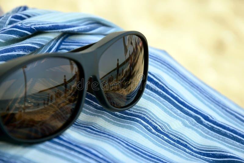 Θερινές διακοπές, παραθαλάσσιες διακοπές Αντανάκλαση στα γυαλιά ηλίου - σκιαγραφίες των ανθρώπων που κάνουν ηλιοθεραπεία από τη θ στοκ φωτογραφία