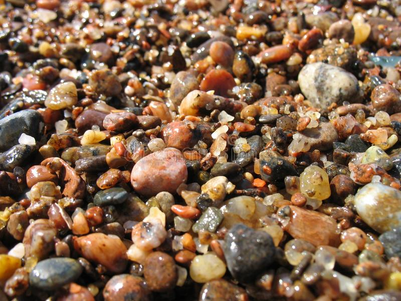 Θερινές υγρές πέτρες και στενός επάνω χαλικιών παραλιών άμμου στοκ εικόνα με δικαίωμα ελεύθερης χρήσης