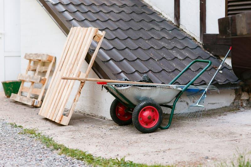 θερινή άνοιξη καροτσακιών τσουγκρανών εργαλείων κήπων κόκκινες ρόδες στέγη υπογείων στοκ εικόνα με δικαίωμα ελεύθερης χρήσης