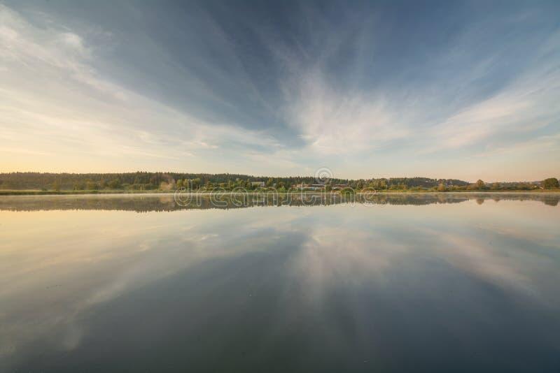 Θερινή αυγή πέρα από τη λίμνη Ο ορίζοντας είναι ακριβώς στη μέση Δημιουργεί μια επίδραση καθρεφτών στοκ εικόνα