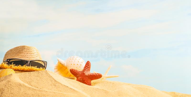 Θερινή περίοδο, θαλασσινό κοχύλι, αστερίας, γυαλιά ηλίου και καπέλο αχύρου στην αμμώδη παραλία με το ηλιόλουστα ζωηρόχρωμα υπόβαθ στοκ φωτογραφία με δικαίωμα ελεύθερης χρήσης
