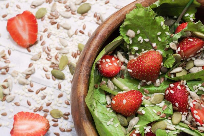 Θερινή σαλάτα διατροφής με τις φράουλες, το μαρούλι και τους σπόρους, ένα ελαφρύ πρόχειρο φαγητό, υγιή τρόφιμα, στοκ φωτογραφίες