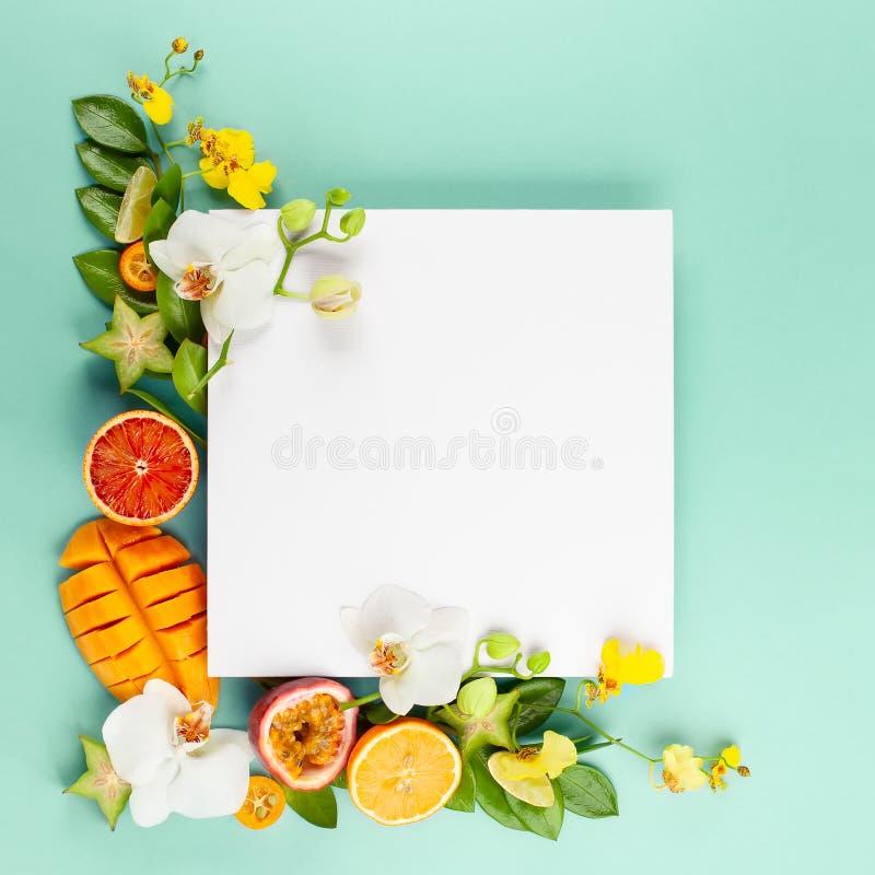 Θερινή σύνθεση με τα φρούτα και τα λουλούδια στο μπλε υπόβαθρο στοκ φωτογραφία