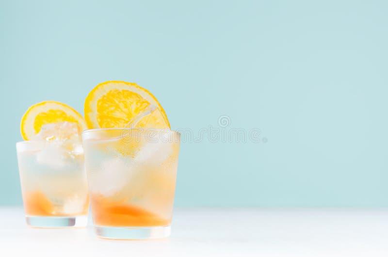 Θερινοί οινοπνευματώδεις χυμοί με το ποτό πορτοκαλιών, κύβοι πάγου στο πυροβοληθε'ν γυαλί στον μπλε τοίχο, διάστημα αντιγράφων στοκ φωτογραφίες με δικαίωμα ελεύθερης χρήσης
