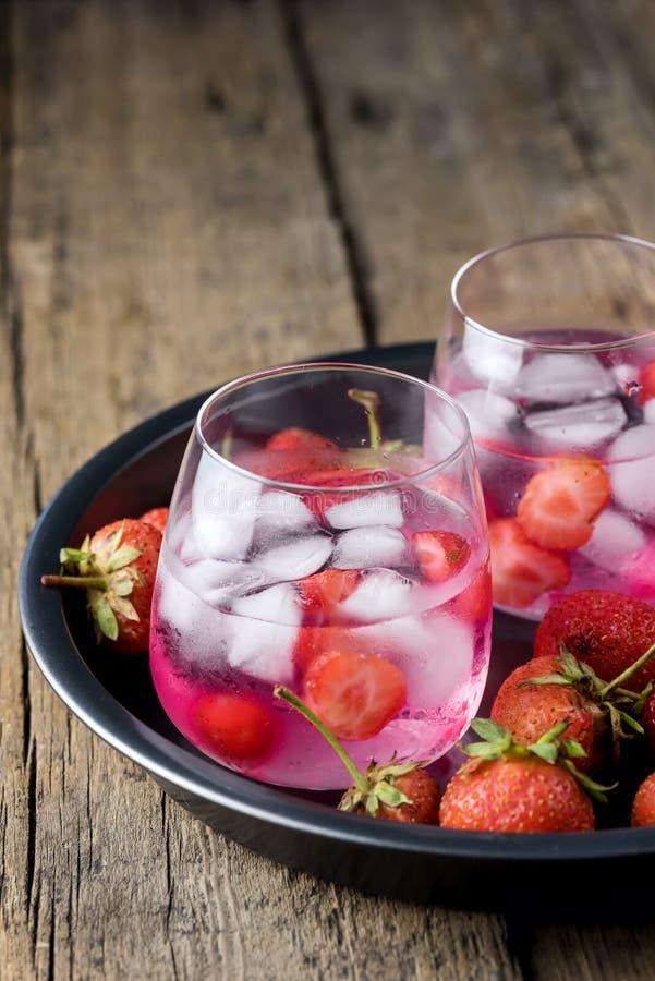 Θερινού φρέσκια αρωματική εμποτισμένη νερού φραουλών Detox φρέσκια φράουλα κύβων πάγου ποτών διατροφής νερού υγιής στο μαύρο πιάτ στοκ φωτογραφία με δικαίωμα ελεύθερης χρήσης
