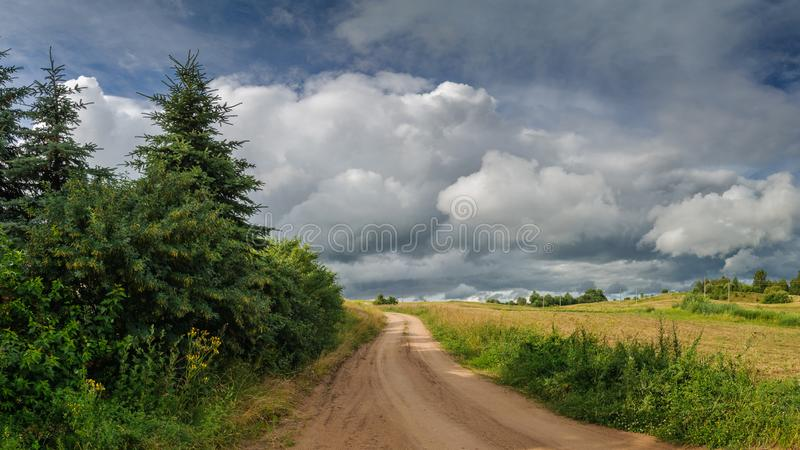 Θερινό αγροτικό τοπίο μη λιθοστρωμένος δρόμος τομέων στο νεφελώδη καιρό πριν από τη βροχή στοκ εικόνα με δικαίωμα ελεύθερης χρήσης