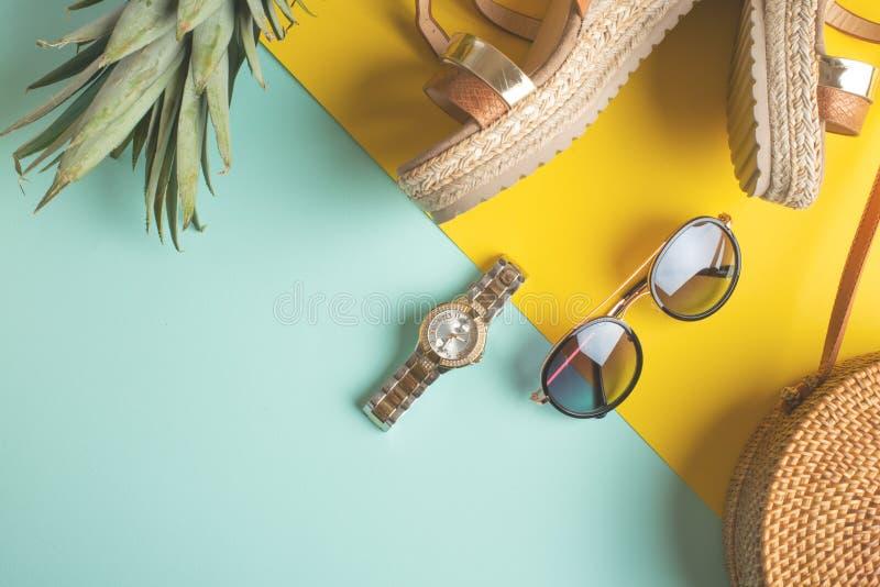 Θερινό ζωηρόχρωμο υπόβαθρο με την ψάθινη τσάντα μόδας, τα τροπικά παπούτσια ανανά και των γυναικών και τα γυαλιά και τα ρολόγια ή στοκ εικόνες