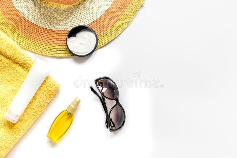 Θερινό καλλυντικό με προστασίας κρέμας και καπέλων την άσπρη χλεύη άποψης υποβάθρου τοπ επάνω στοκ εικόνα