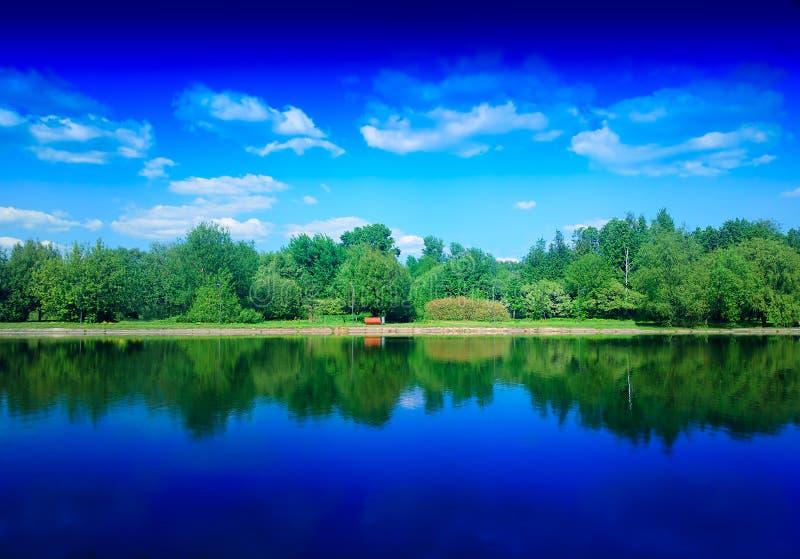 Θερινό πάρκο στον ποταμό με το δραματικό υπόβαθρο αντανακλάσεων στοκ φωτογραφία με δικαίωμα ελεύθερης χρήσης