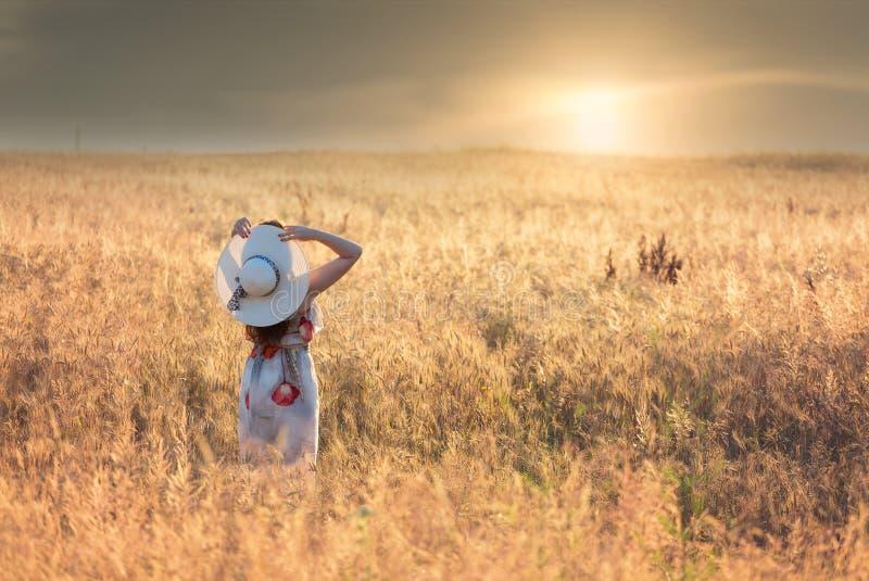 Θερινό πορτρέτο μιας νέας γυναίκας, που φορά ένα άσπρο καπέλο, στον τομέα σίτου, στο ηλιοβασίλεμα στοκ εικόνες