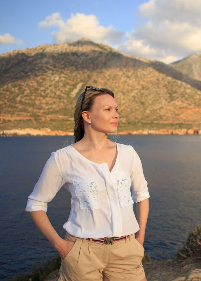Θερινό πορτρέτο του όμορφου κοριτσιού που στέκεται κοντά στη θάλασσα και το τοπίο βουνών στοκ φωτογραφία με δικαίωμα ελεύθερης χρήσης