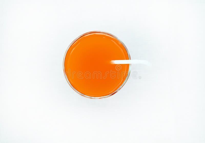 Θερινό ποτό - ο πρόσφατα συμπιεσμένος χυμός γκρέιπφρουτ σε ένα γυαλί με έναν σωλήνα αχύρου, τοπ άποψη, απομόνωσε σε ένα άσπρο υπό στοκ εικόνα