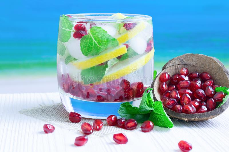 Θερινό ποτό του λεμονιού, του ροδιού και της μέντας σε έναν άσπρο ξύλινο πίνακα ενάντια στη θάλασσα στοκ εικόνες
