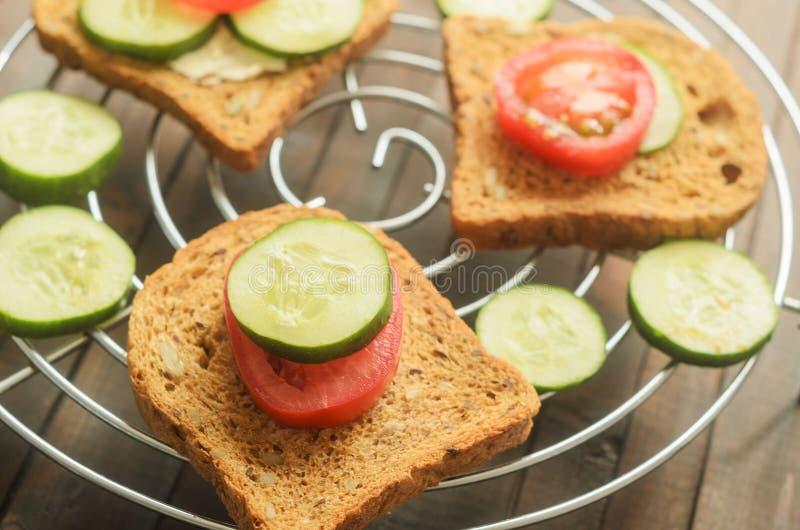 Θερινό σάντουιτς με μια φέτα του αγγουριού και μια φέτα της ντομάτας στη σχάρα στο υπόβαθρο των άλλων δύο σάντουιτς και στοκ φωτογραφία