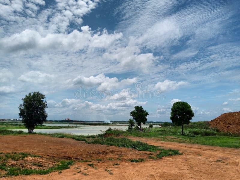 Θερινό τοπίο με τον πράσινο τομέα κάτω από τα σύννεφα στον ουρανό στοκ φωτογραφία