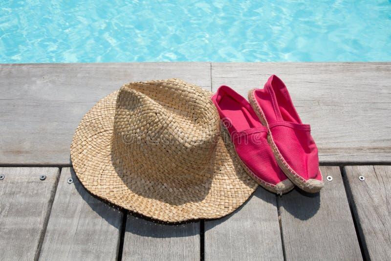 Θερινό υπόβαθρο με τα παπούτσια καπέλων στην ξύλινες γέφυρα και τη λίμνη στοκ φωτογραφία