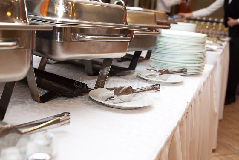 Θερμάστρα πιάτων σκαρών στο συμπόσιο στοκ εικόνες