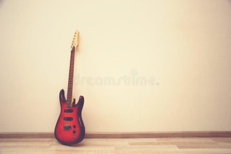 Θερμή αναδρομική τονισμένη φωτογραφία της ηλεκτρο κιθάρας που στέκεται κοντά wal στοκ εικόνα με δικαίωμα ελεύθερης χρήσης