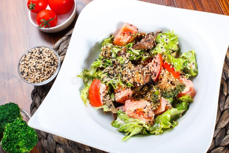 Θερμή σαλάτα με το συκώτι κοτόπουλου, ντομάτες, φύλλα μαρουλιού, μπρόκολο στον ξύλινο πίνακα στοκ φωτογραφία