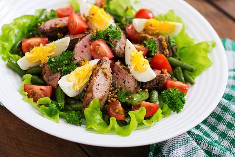 Θερμή σαλάτα με το συκώτι κοτόπουλου, πράσινα φασόλια, αυγά, ντομάτες στοκ εικόνα
