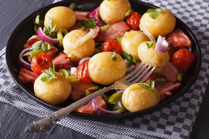 Θερμή σαλάτα των καινούριων πατατών με το μπέϊκον και τα λαχανικά, στοκ φωτογραφία