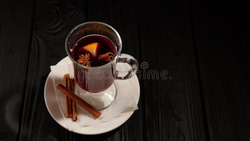 Θερμαμένο κρασί στο άσπρο πιάτο στο μαύρο ξύλινο πίνακα, τα ραβδιά κανέλας και την πορτοκαλιά, τοπ άποψη στοκ φωτογραφίες με δικαίωμα ελεύθερης χρήσης